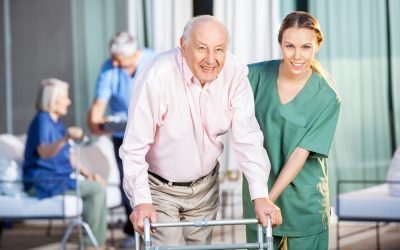 Portrait of happy female caretaker helping senior man in using Zimmer frame at nursing home yard